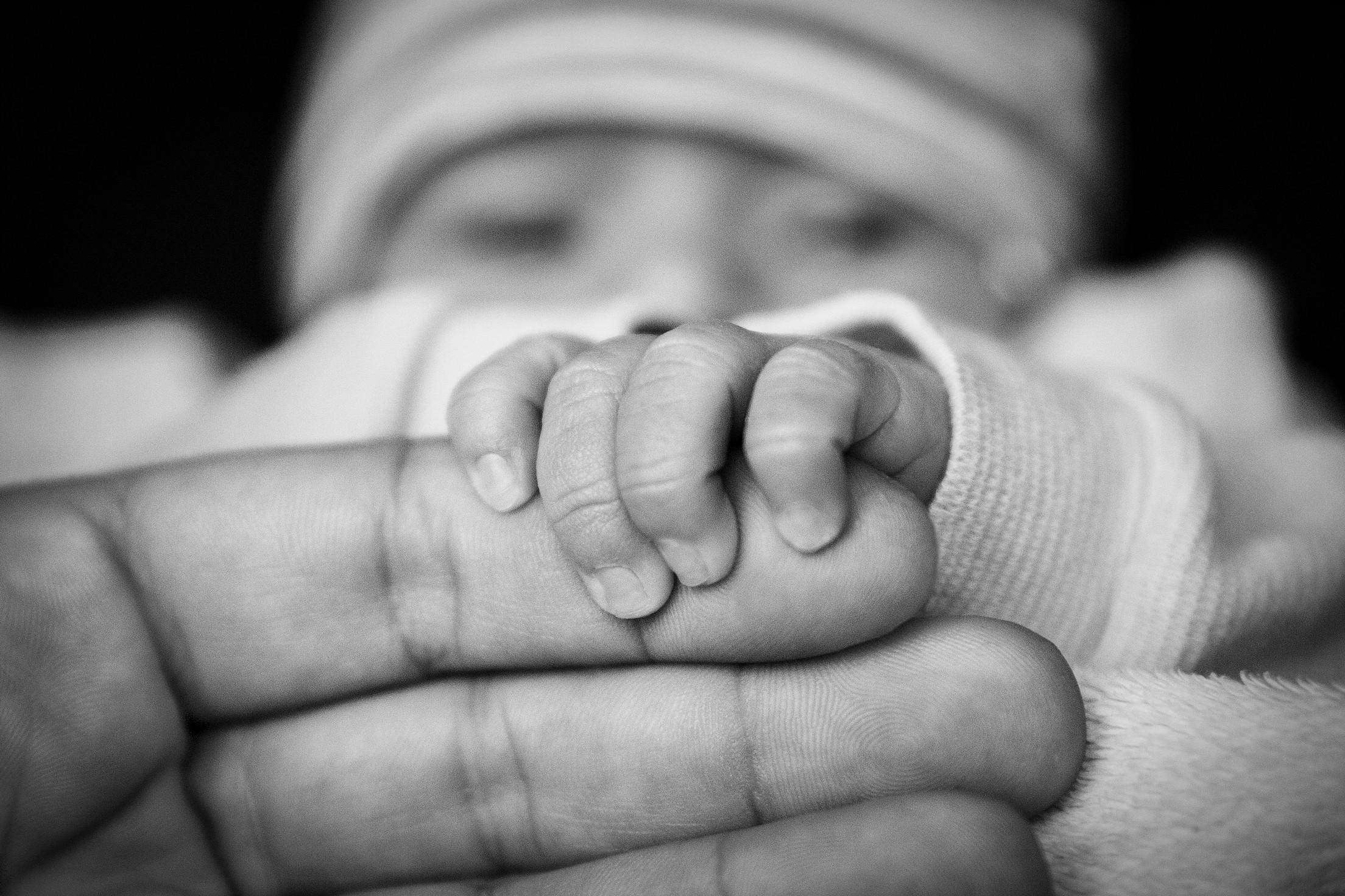 Infant holding man's hand